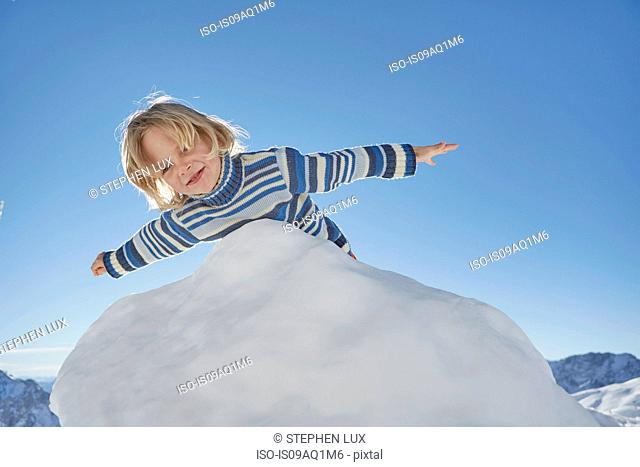 Young boy leaning over pile of snow, low angle view