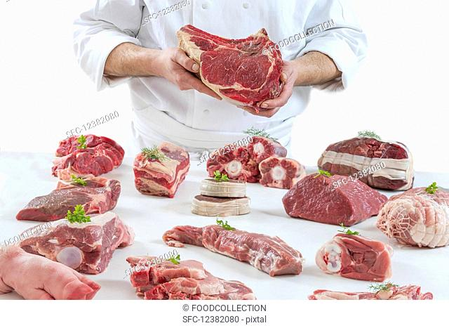 A chef presenting different types of fresh raw meat