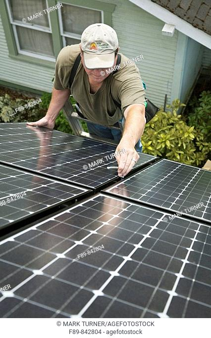 Man bolts solar panel into array