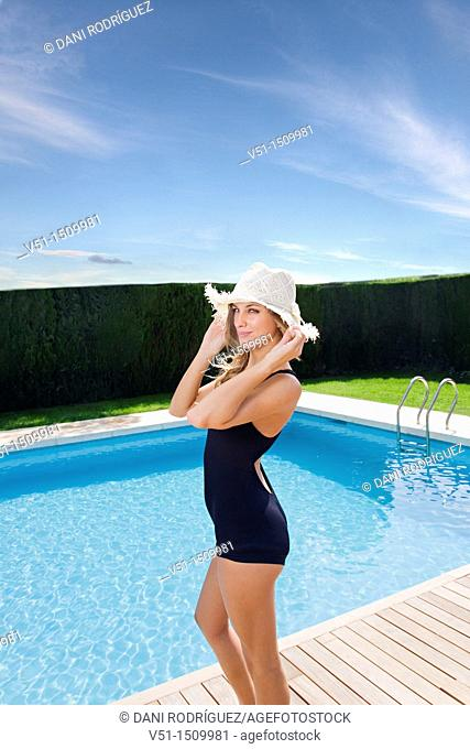 Sexy blonde woman in swimsuit with hat by the pool looking at camera
