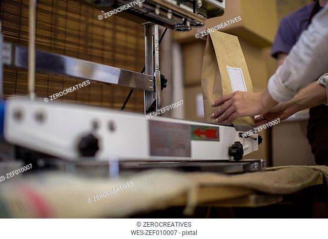 Woman working at coffee bean packaging vacuum sealer