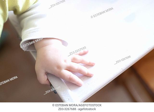 baby hand on white wood table