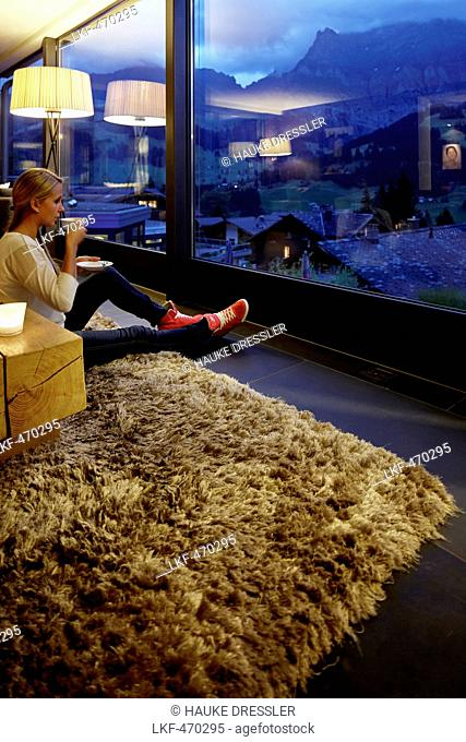 Woman sitting on floor in a hotel winter garden while enjoying view in the evening, Adelboden, Canton of Bern, Switzerland