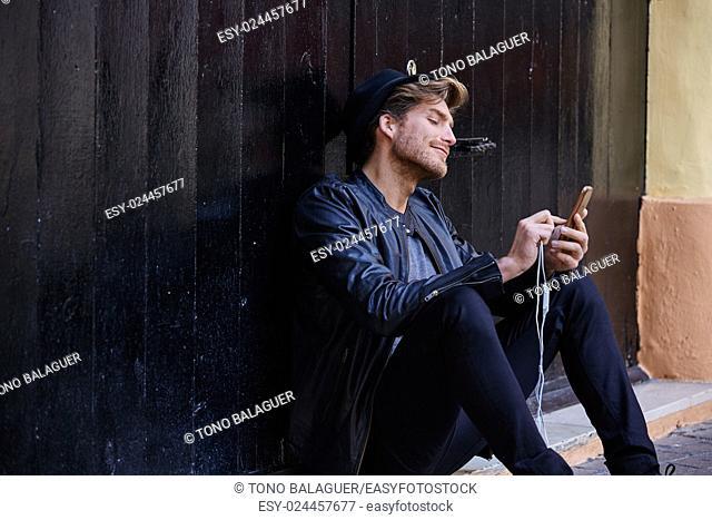 Young man with smartphone earphones sitting in the street black door