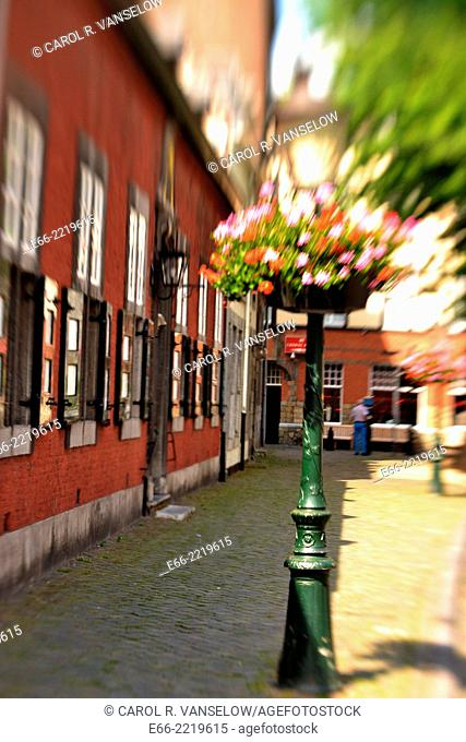Lamppost decorated with flower basket on a side street in Maastricht