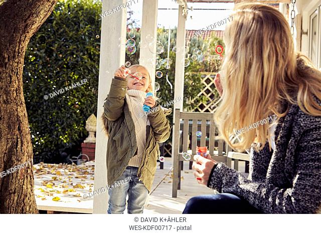 Happy girl with mother in garden making soap bubbles
