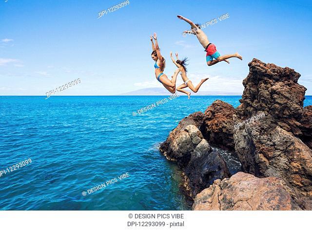 Summer fun, Friends cliff jumping into the ocean