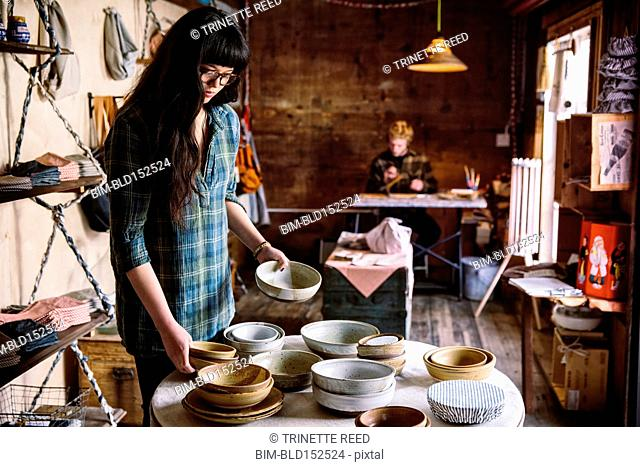 Mixed race business owner holding bowls in shop