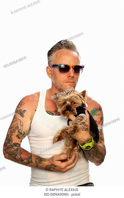 Mature man holding teacup Yorkshire terrier against white background