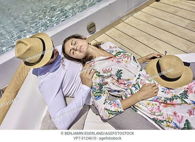 couple relaxing on sunbeds next to pool, summer, holidays