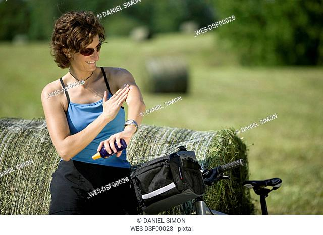Germany, Bavaria, Seeshaupt, Woman with mountain bike applying sun cream