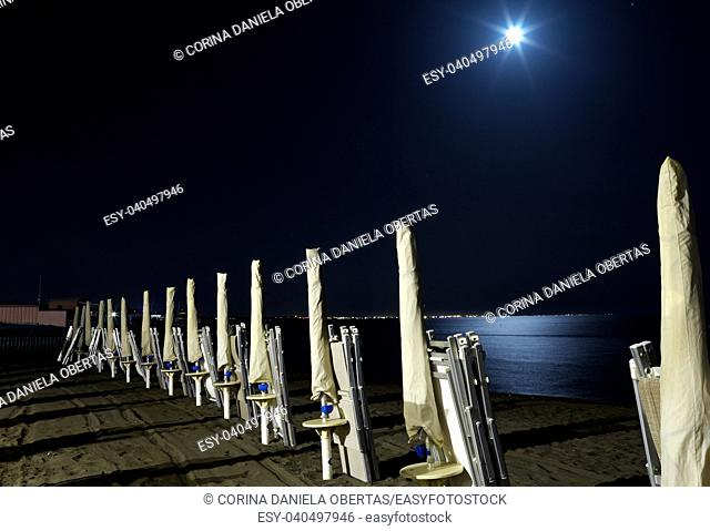Empty beach at night with full moon reflecting in the sea, Marina di San Nicola, Lazio, Italy