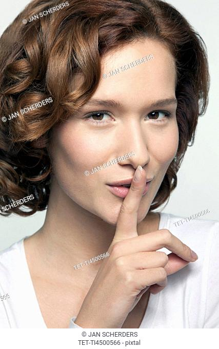 Studio shot portrait of young woman in white blouse with finger on lips