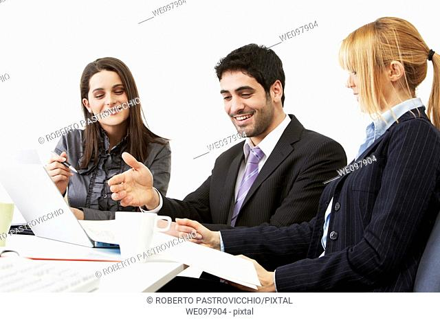 Happy business people in a meeting working on a laptop