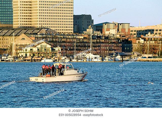 U.S. Coastguard ship patrols Boston Harbor and the Boston skyline from terrorists at sunrise as seen from South Boston, Massachusetts, New England