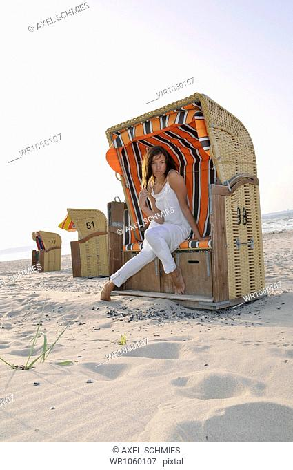 Young woman, 24, in a beach chair, Niendorf, Baltic Sea, Schleswig-Holstein, Germany, Europe