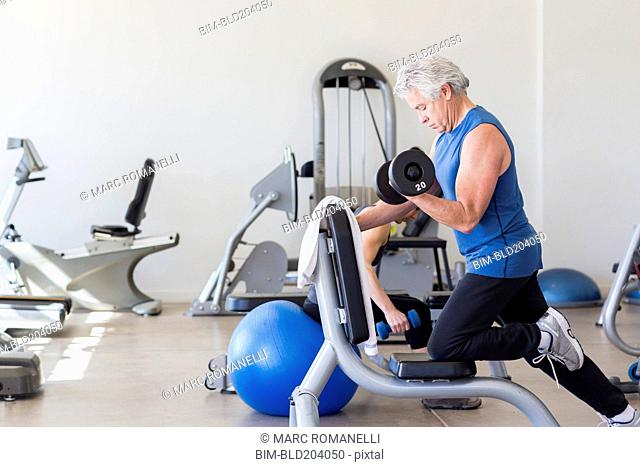 Older Hispanic man lifting weights in gym