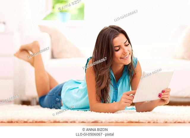 Happy woman relaxing at home with digital tablet, Debica, Poland
