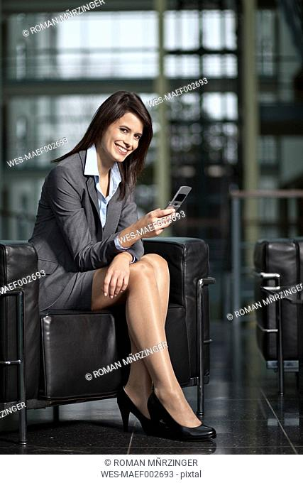 Germany, Bavaria, Business woman with mobile, smiling, portrait
