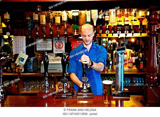 Barman standing behind bar in pub