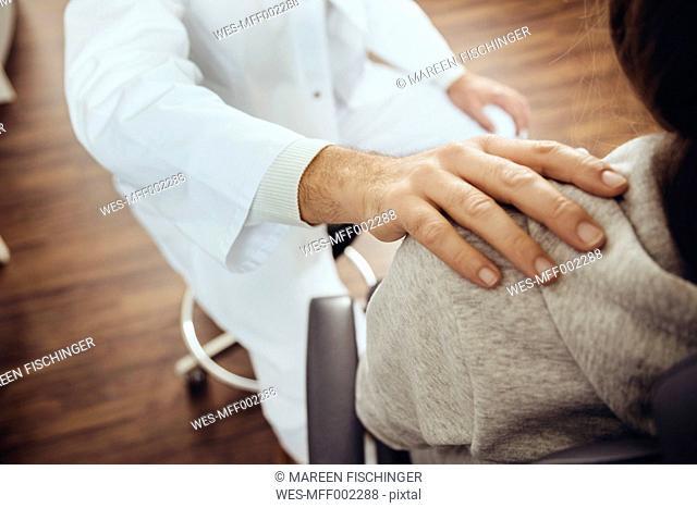 Doctor putting hand on teenage patient's shoulder