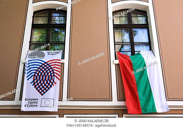 "14.09.2018, Bulgaria, Plovdiv: A flag bearing the logo of the European Capital of Culture 2019 under the motto """"Together"""" and a flag of Bulgaria hanging from..."
