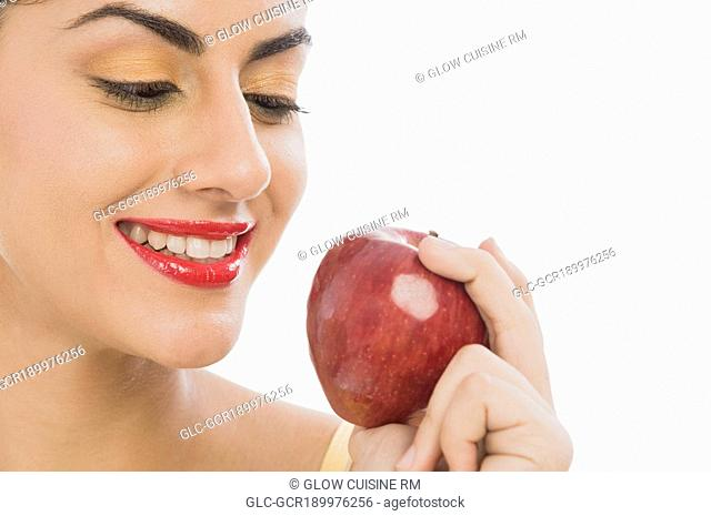 Close-up of a woman holding a red apple and smiling