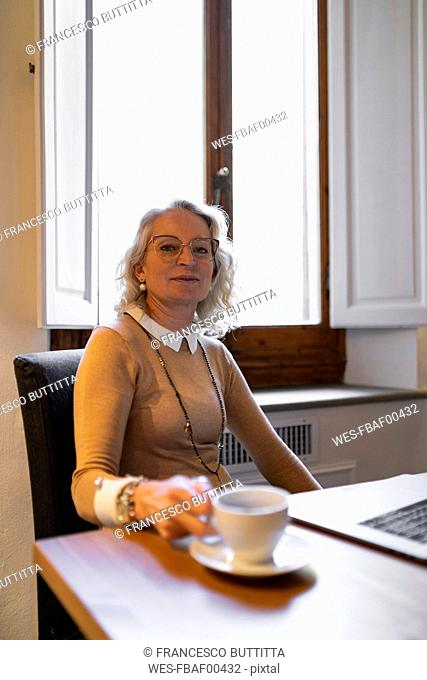 Portrait of content mature businesswoman sitting at table with laptop and cup of coffee