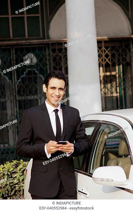 Portrait of businessman with mobile phone , INDIA , DELHI