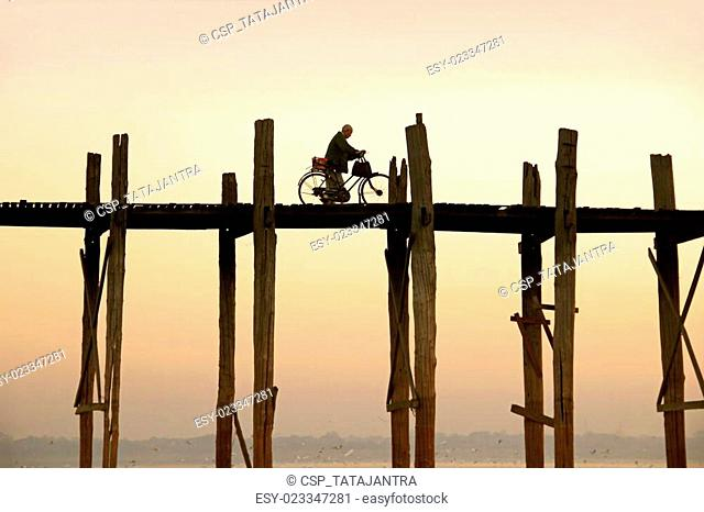 cyclist is driving over U Bein's Bridge