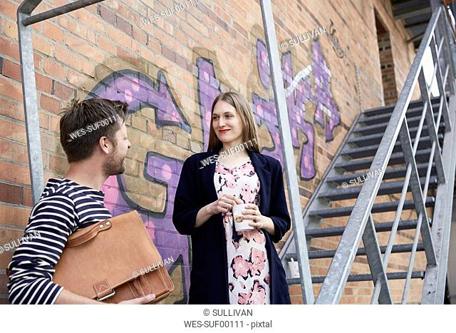 Smiling man with bag looking at woman on stairs