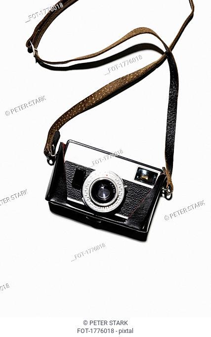 Retro camera and strap on white background