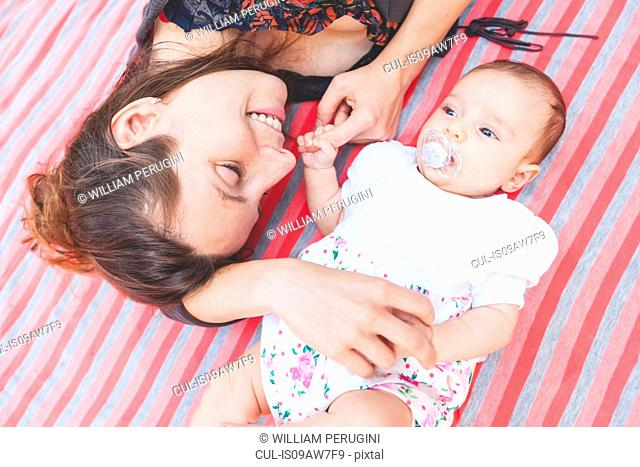 High angle view of mother and baby girl lying down on blanket