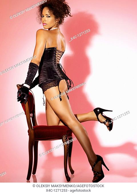 Beautiful woman in black corset posing with a chair on pink background