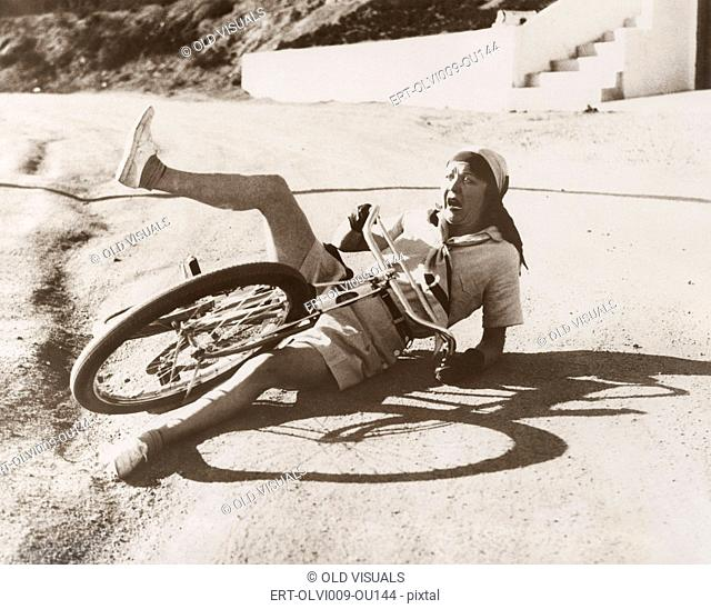 Woman falling off her bicycle on side of road