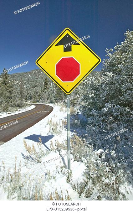 Snowy road with yellow sign warning to stop ahead
