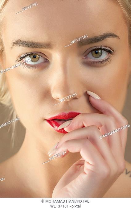 Beautiful young woman hand touching lips