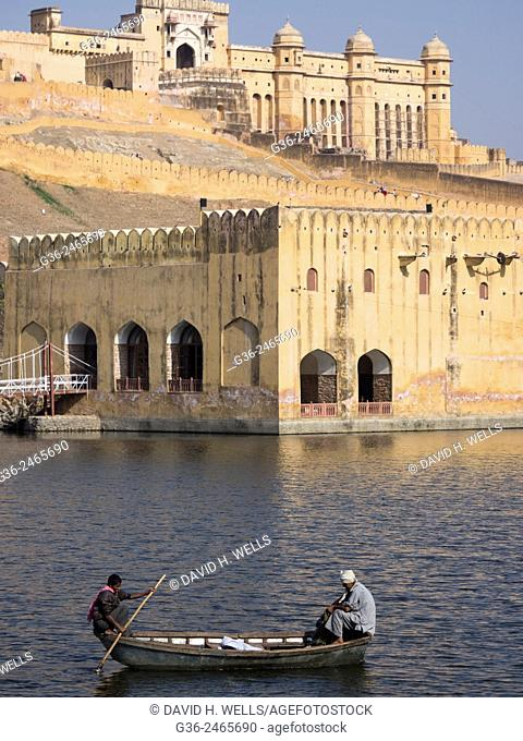 Men travelling on boat in front of Amer Palace in Jaipur, Rajasthan, India
