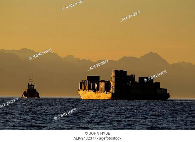 A tug and barge in Lynn Canal hauling containers of goods towards Haines, Alaska, peaks of the Chilkat Range beyond