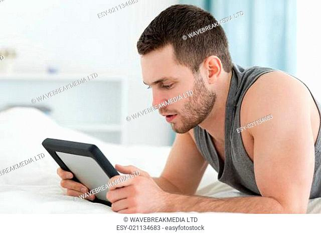 Man using a tablet computer while lying on his belly