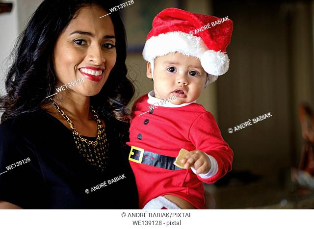 Close up of hispanic woman holding her baby boy, dressed in Christmas outfit eating a cookie