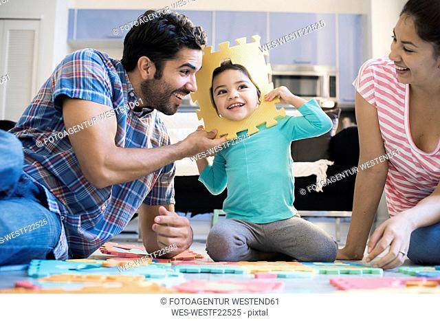Happy family sitting on floor, playing with daughter