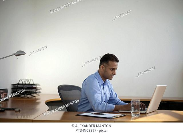 Singapore, Businessman working at laptop in office