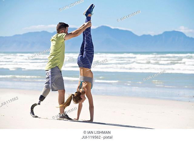 Man Wearing Prosthetic Blade Helping Woman To Do Handstand On Beach