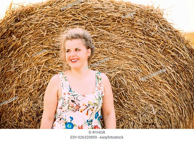 Beautiful Plus Size Young Woman In Shirt Posing In Summer Field Meadow Near Hay Bales At Sunset Background