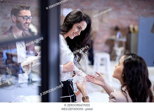 Dressmakers with client in fashion showroom trying on wedding dress