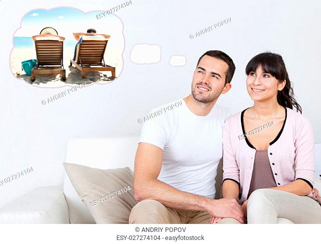 Happy young couple dreaming about the future at home