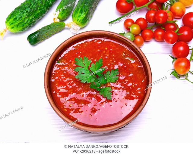 Cold tomato soup gazpacho from fresh tomato and vegetables in a brown round plate on a white wooden table, top view