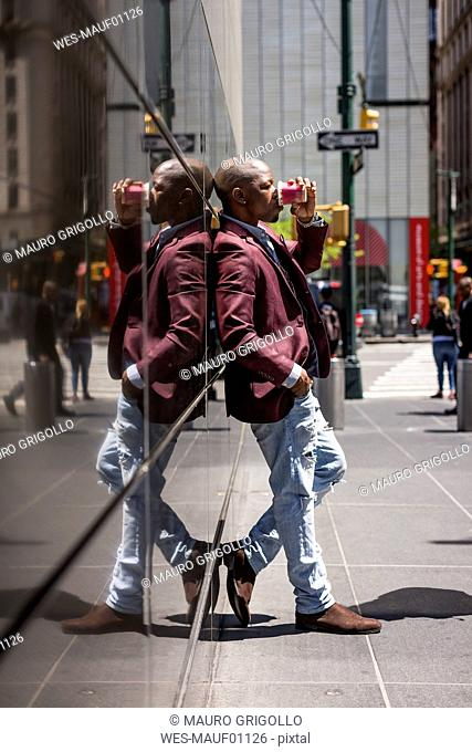 USA, New York City, Manhattan, stylish businessman with coffee to go leaning against glass facade