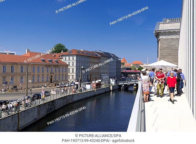 13 July 2019, Berlin: Visitors are standing on the terrace after the opening of the James Simon Gallery. On the left the houses at the Kupfergraben next to the...